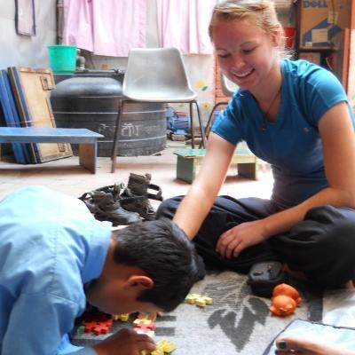 A child and Projects Abroad student work on an activity on the Physiotherapy internship for teenagers in Nepal.